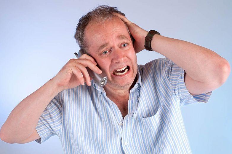 зрелый мужчина говорит по телефону