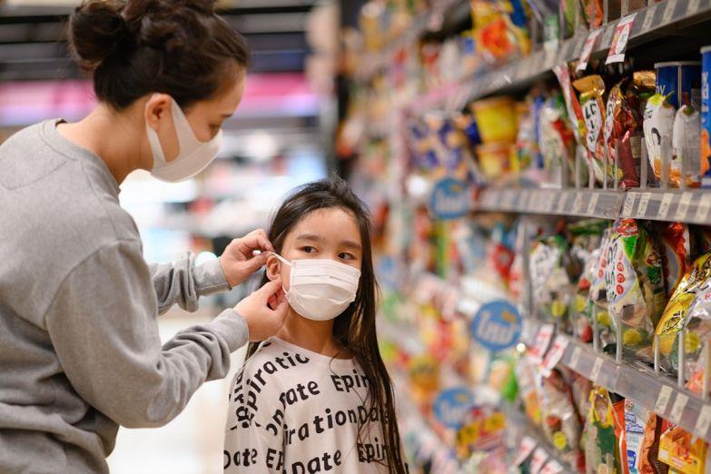 женщина надевает маску ребенку