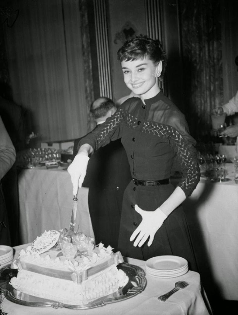 Одри Хепберн позирует с тортом во время коктейльной вечеринки в ее честь.