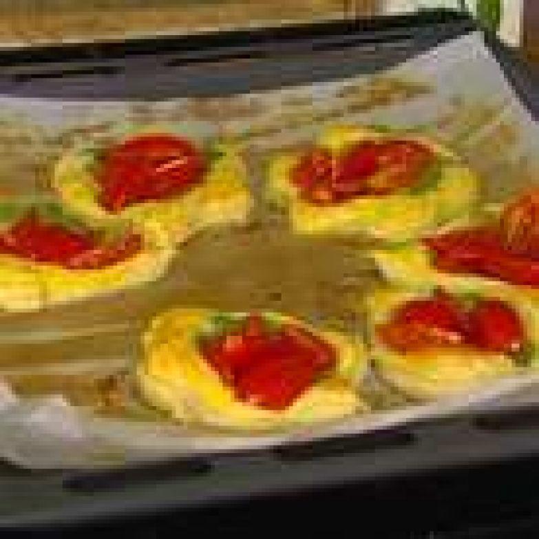В центр каждой фигурки из теста выложить понемногу соуса песто и несколько долек помидора, сбрызнуть оливковым маслом и отправить противень в разогретую духовку.