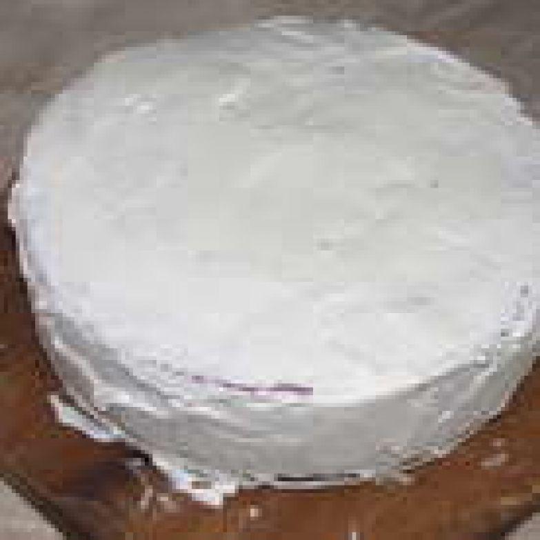Взбить оставшиеся сливки, постепенно добавляя сахарную пудру, и обмазать торт со всех сторон.