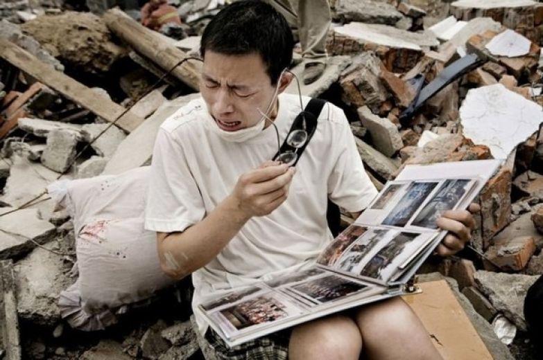 Парень смотрит семейный альбом, который нашел в щебне своего старого дома после землетрясения в Сычуани. история, события, фото