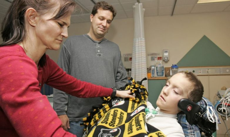 "FILE - In this Jan. 9, 2009 file photo, Beth Malarkey, left, covers up her son, Alex, right, with a blanket after surgery as Alex's father, Kevin, watches at University Hospital's Case Western Reserve Medical Center in Cleveland. Alex Malarkey was in a 2004 car crash left him paralyzed below the neck and was receiving an artificial breathing device. Spokesman Todd Starowitz of Tyndale House, a leading Christian publisher, confirmed Friday, Jan. 16, 2015, that Alex Malarkey's ""The Boy Who Came Back from Heaven: A Remarkable Account of Miracles, Angels, and Life Beyond This World"" was being withdrawn. Earlier this week, Alex Malarkey acknowledged in an open letter that he was lying, saying that he had been seeking attention. The book was first published in 2010. (AP Photo/Tony Dejak, File)"