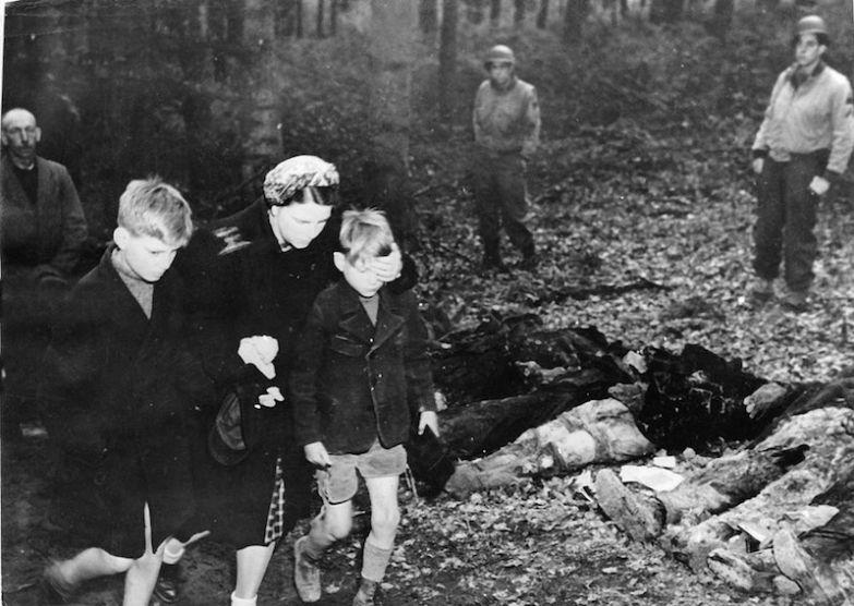 Мать-немка закрывает глаза сыну, когда они проходят мимо эксгумированных тел 57 русских солдат, 3 мая 1945