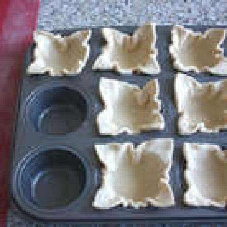 Металлическую форму смазать маслом, выложить в неё 12 квадратиков слоёного теста так, чтобы уголки оставались свободными.