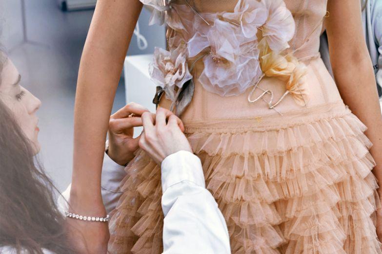 Швея создает цветочную композицию на платье прямо во время примерки