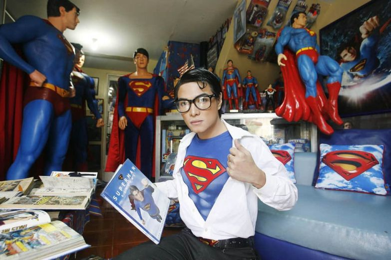 """Herbert Chavez poses with his Superman collection inside his house in Calamba Laguna, Philippines. In his idolization of the superhero, Chavez, a self-professed """"pageant trainer"""" who owns two costume stores, has undergone a series of cosmetic surgeries for his face, body, and even his skin color to look more like the """"Man of Steel""""."""