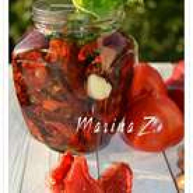 Сложить вяленые помидорки в стерилизованную баночку, добавить несколько зубчиков чеснока и пару веточек лимонного базилика (у меня баночка на 0,5 л). Залить оливковым маслом и добавить 1 чайную ложку бальзамического уксуса.