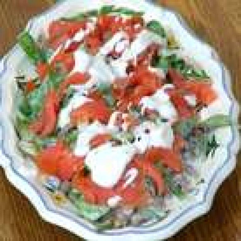 Форель нарезать небольшими кусочками, выложить на салат и полить все оставшейся заправкой.