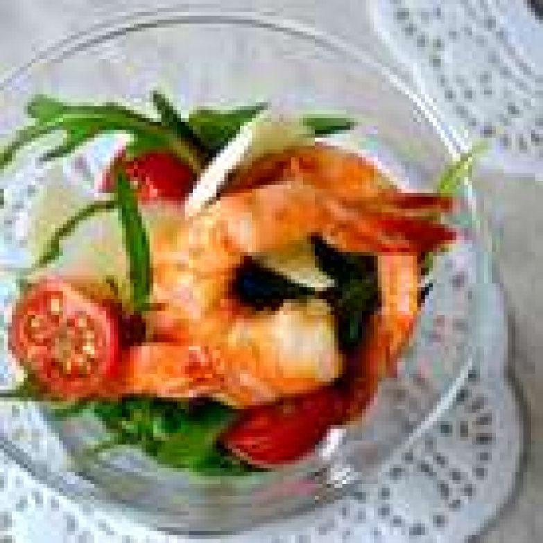 В салатник (можно порционно, как у меня) выложить руколу, помидоры, сверху выложить креветки и добавить пластинки пармезана. Сбрызнуть маслом, в котором обжаривались креветки и несколькими каплями бальзамического уксуса.