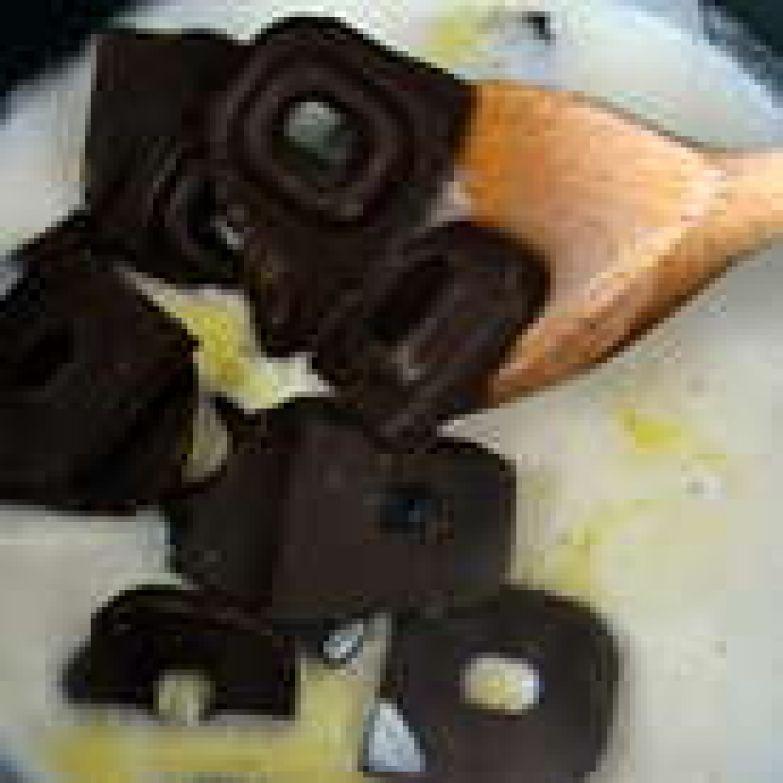 Не доводя до активного кипения сливки, добавить в кастрюльку кусочки шоколада. Помешивая деревянной ложкой, дать шоколаду полностью раствориться, масса немного загустеет. Отставить ганаш с огня и дать остыть... Далее, по рецепту предлагалось сразу нанести ганаш на торт. Первый раз я так и сделал, но мне показалось, что глазурь получилась слишком жидкой... В общем, я не до конца осталась довольна украшением. (((