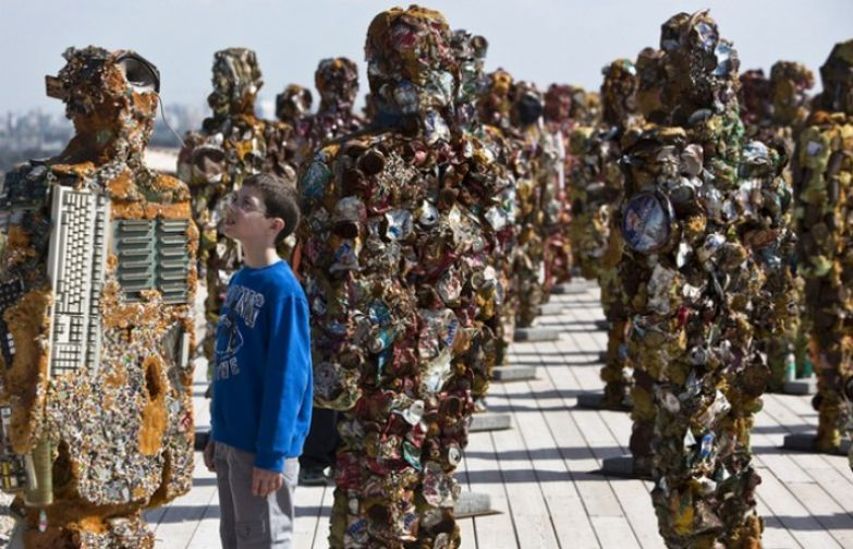 "A boy looks at a statue by German artist HA Schult during a preview of the artist's exhibition at the Ariel Sharon Park near Tel Aviv April 2, 2014. Schult's ""Trash People"" exhibition, featuring 500 human-sized figures made from recycled materials, has been travelling worldwide for 18 years and opens this weekend near Tel Aviv. (Photo by Nir Elias/Reuters)"