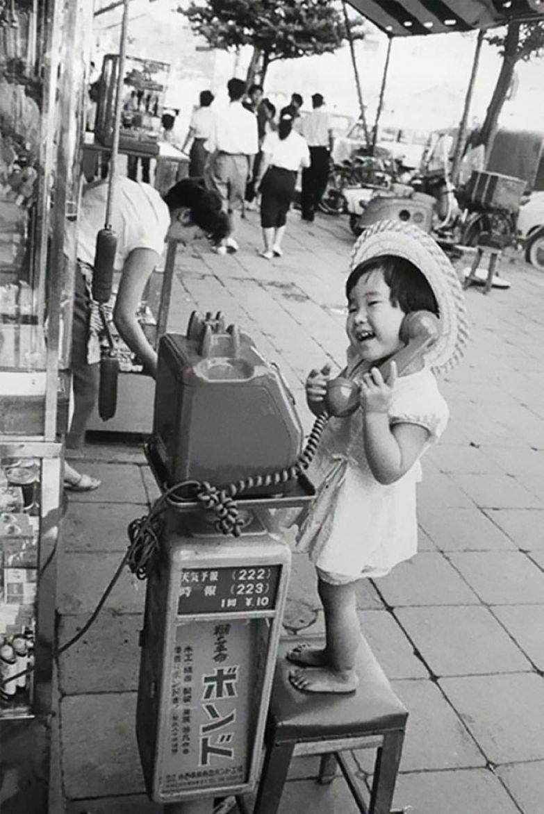 19. Девочка веселится, изображая разговор по телефону. Япония, 1958 г. архивные фотографии, лучшие фото, ретрофото, черно-белые снимки