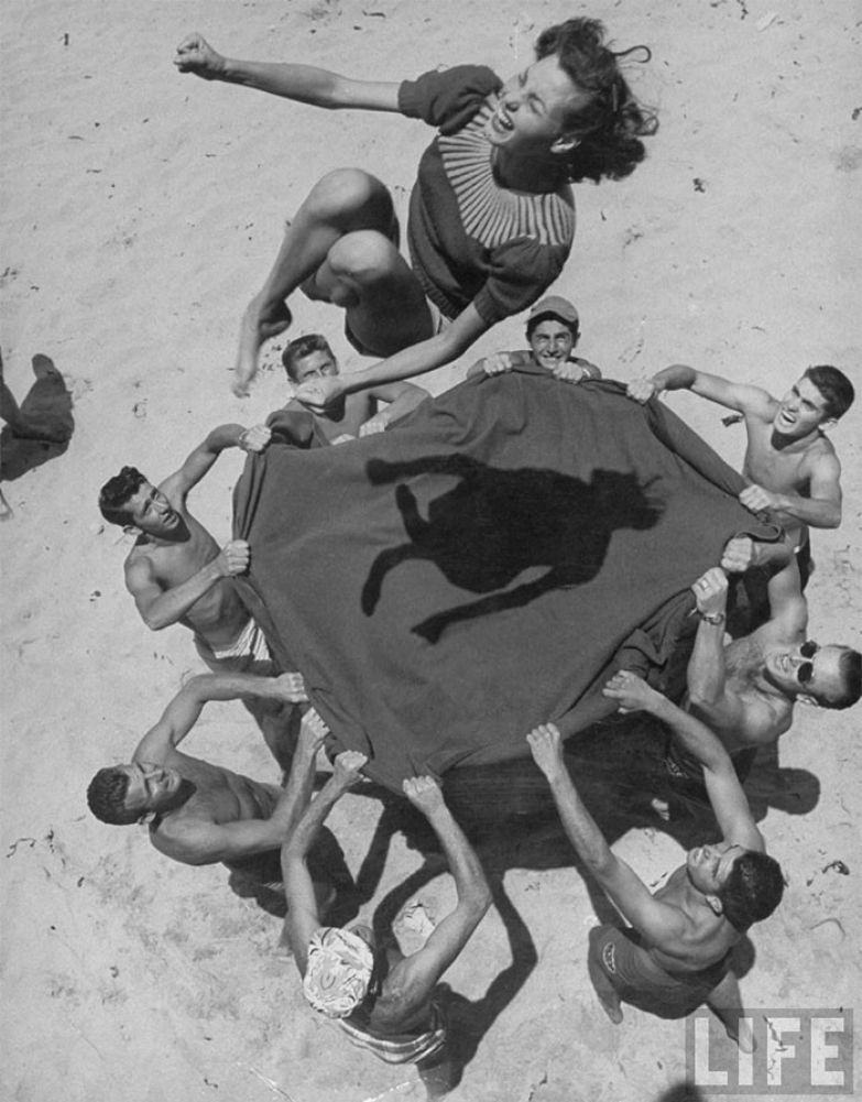28. Парни подбрасывают свою подругу Норму Бейкер в воздух на пляже, 1948 г. архивные фотографии, лучшие фото, ретрофото, черно-белые снимки