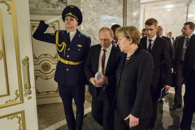 После перерыва во время переговоров по урегулированию украинского конфликта в Минске. Канцлер Меркель и президент России Владимир Путин возвращаются за стол переговоров 11 февраля 2015 года.