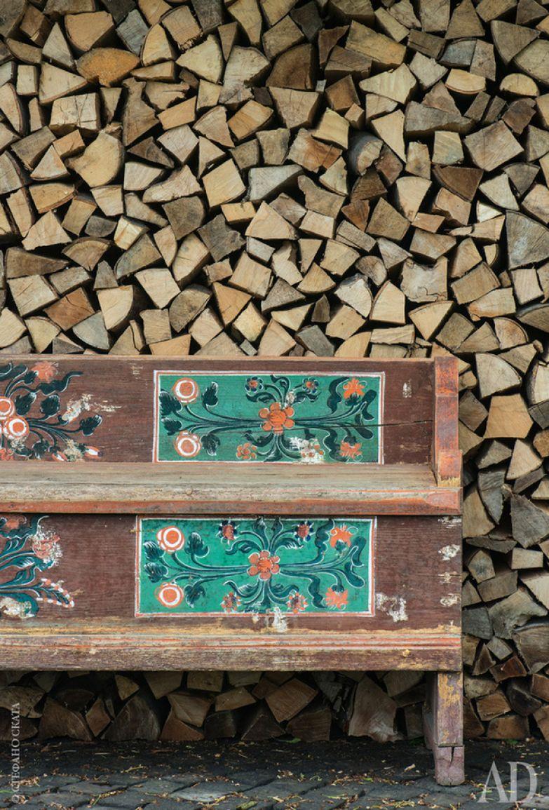 Поленница выглядит как продуманный фон для скамейки, расписанной местными мастерами.
