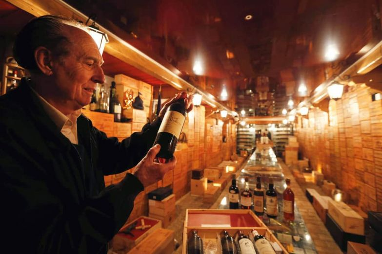 French collector Michel-Jack Chasseuil shows off a bottle of wine in his wine cellar as he presents his collection of rare and prestigious vintages in La Chapelle-Baton, France. Michel-Jack Chasseuil has amassed more than 40,000 bottles over his lifetime.
